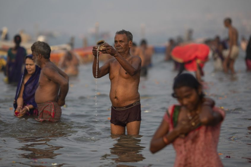 An Indian Hindu pilgrim prays at Sangam, the confluence of the rivers Ganges, Yamuna and mythical Saraswati, during the Kumbh Mela festival in Allahabad, India.