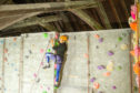 Gayle Ritchie reaches the top of a climbing wall at Avertical World in Dundee.