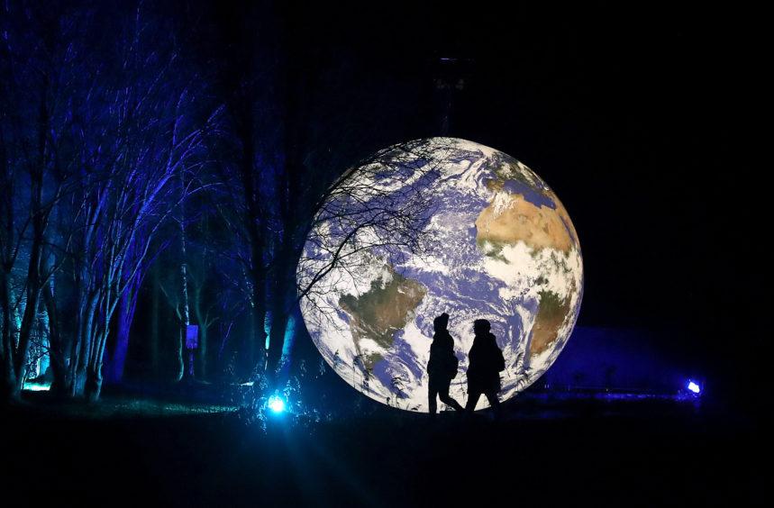 Visitors walks past the art installation Gaia.