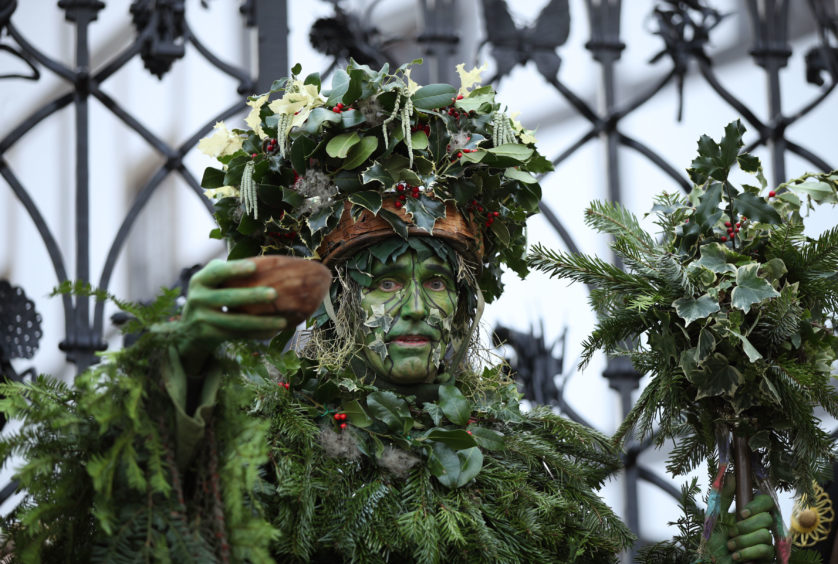To herald the celebration, the extraordinary Holly Man, the winter guise of the Green Man (seen on pub signs, pagan myths and folklore), decked in fantastic green garb and evergreen foliage, is piped over the River Thames.