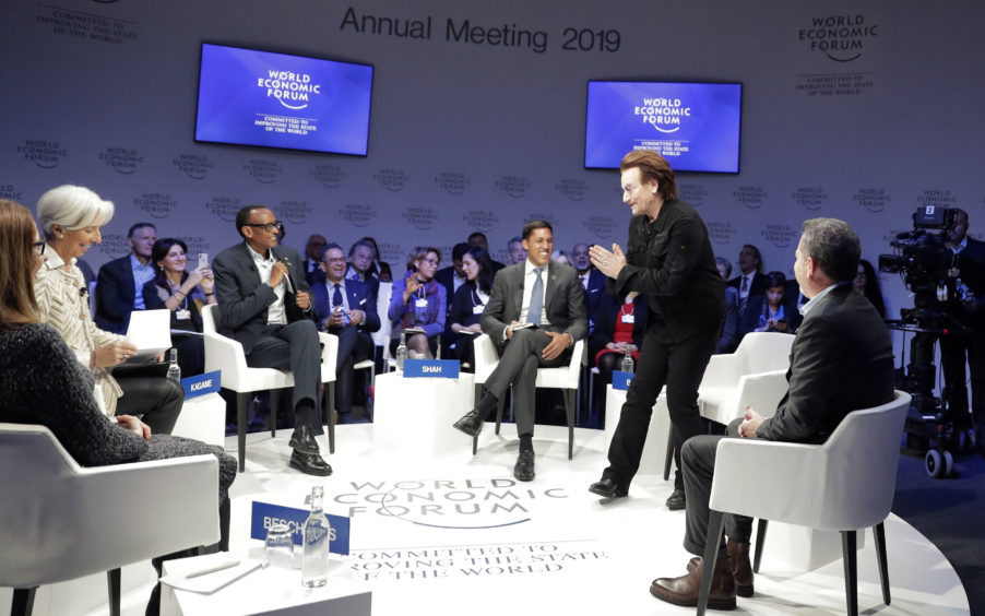"""Singer and co-founder of RED Bono, 2nd right, gestures to Afsaneh Mashayekhi Beschloss, founder of RockCreek, Christine Lagarde, Managing Director of IMF and Rwanda President Paul Kagame, from left, as he arrives for the """"Closing the Financing Gap"""" session at the annual meeting of the World Economic Forum in Davos, Switzerland."""