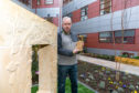 Stone carver Pete Reilly with his sculpture in the Queen Margaret Hospice Garden in Dunfermline.