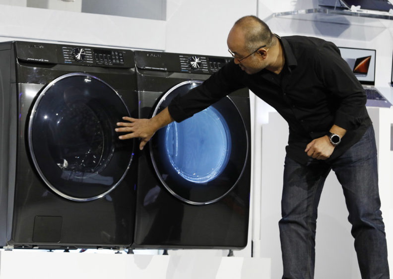Yoon Lee, senior vice president, Samsung Electronics America, looks at a new front-load washer during a Samsung news conference.