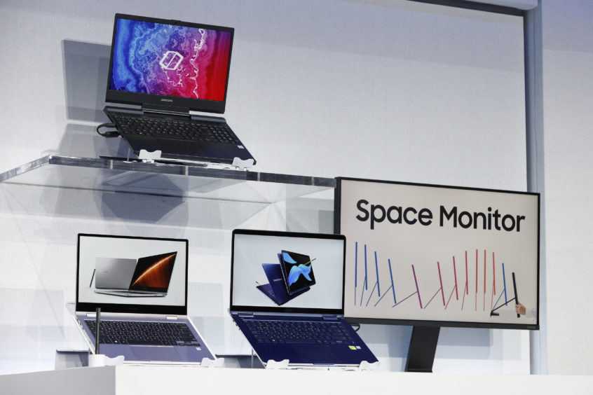 New computers and a monitor are on display during a Samsung news conference.