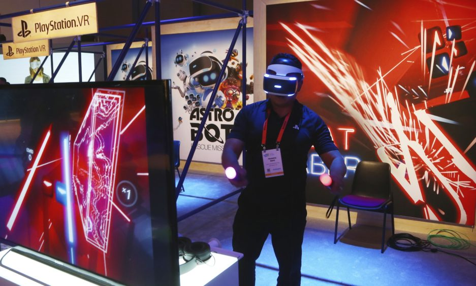 A CES attendee plays the PlayStation VR Beat Saber game inside the Sony display area.
