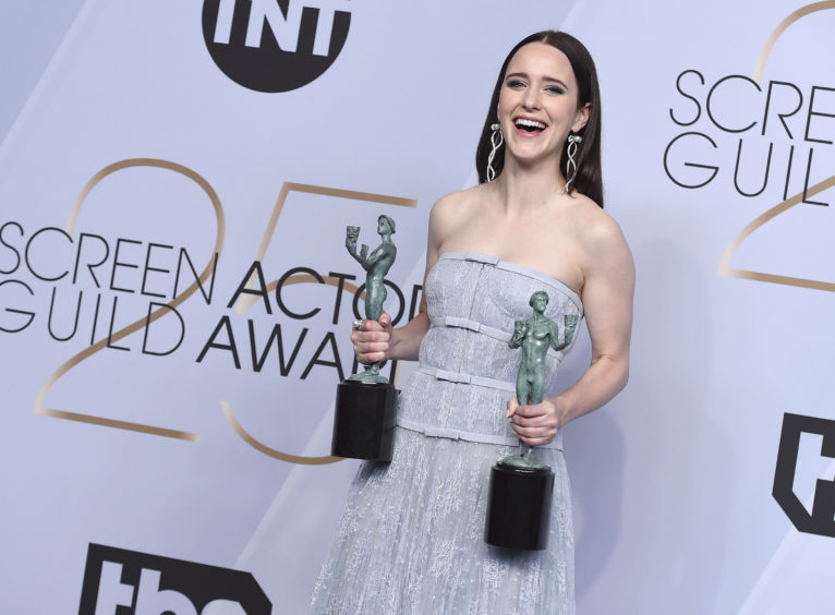Rachel Brosnahan poses with the awards for Outstanding Performance by a Female Actor in a Comedy Series for The Marvelous Mrs. Maisel and for Outstanding Performance by an Ensemble in a Comedy Series for The Marvelous Mrs. Maisel.