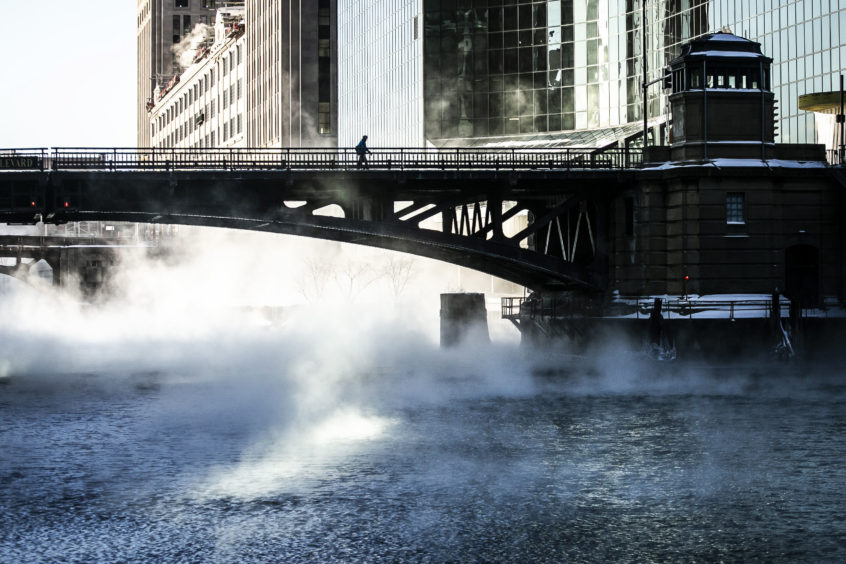 A lone pedestrian crosses the Chicago River early Wednesday, A deadly arctic deep freeze enveloped the Midwest with record-breaking temperatures.