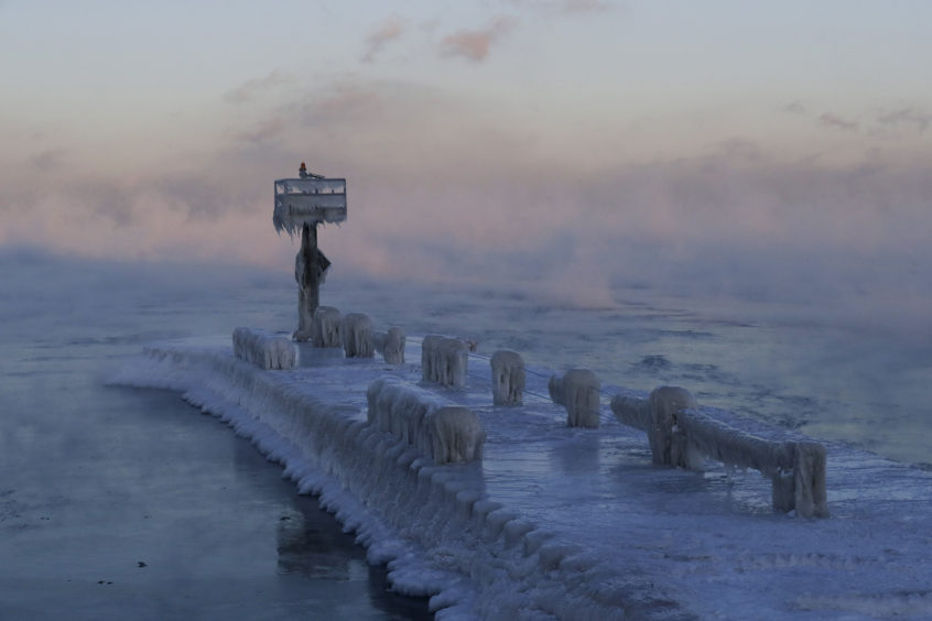 A harbor light is covered with snow and ice on the Lake Michigan at 39th Street Harbor in Chicago. A deadly arctic deep freeze enveloped the Midwest with record-breaking temperatures on Wednesday.