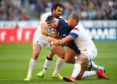Simon Berghan of Scotland is tackled by Gael Fickou and Yoann Huget in Paris.
