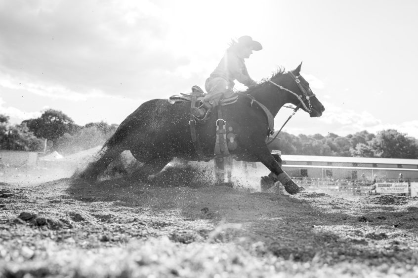 A competitor steers her mount around one of the markers in the barrel race of the Mudgee Show Rodeo in Mudgee, Australia.