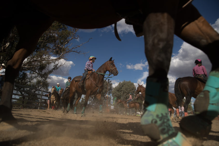 Competitors ride around the holding yard as they wait to ride in the barrel race of the Mudgee Show Rodeo in Mudgee, Australia.