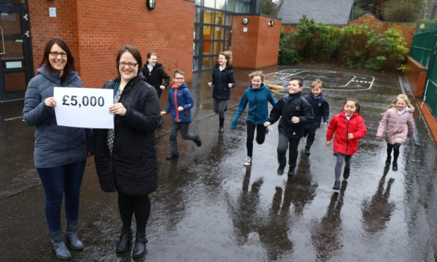 Carole-Ann Porter, left, Co-chairwoman of the Parent Council, with committee member Kate Wardle, and some of the kids, celebrating the £5,000 they have received.