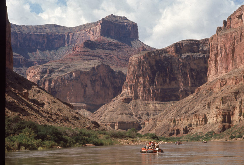 Several rafts full of people float down the Colorado River through the Grand Canyon, Colorado, 1970s.