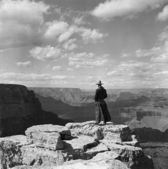 circa 1935:  A cowboy wearing chaps stands on Grandeur Point, East Rim Drive, overlooking the Grand Canyon, Arizona.