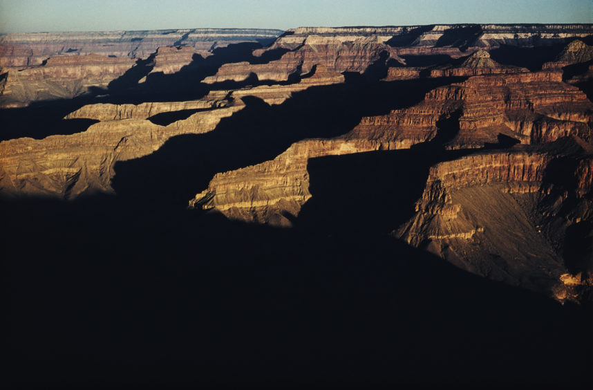 circa 1965:  Black shadows and the sun glinting on rocks, the Grand Canyon at dawn  In America book