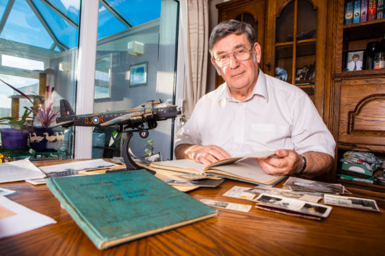 Alan Fraser looks through pictures and official documents in relation to his uncle's RAF service during World War Two.