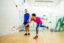 Gayle has a bash at playing squash under the watchful eye of coach Mark Beaumont.
