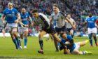 Scotland's Blair Kinghorn runs through for his third try against Italy.