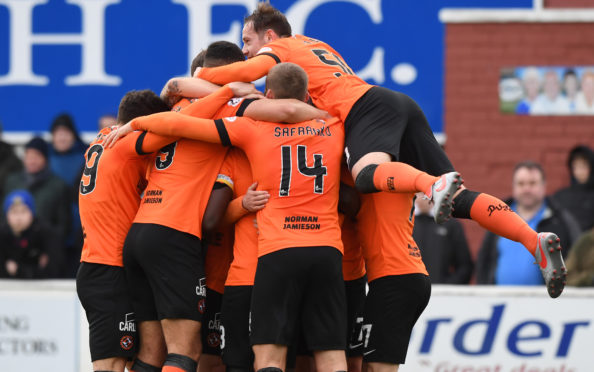 Nicky Clark is joined by his teammates to celebrate the goal.