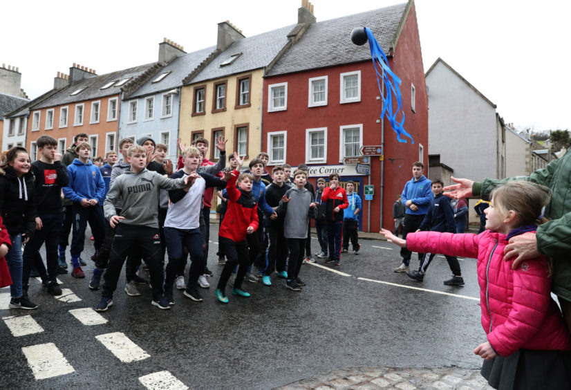 Lois Porterfield from Jedburgh throws in the leather ball during the annual 'FasternÕs E'en Hand Ba' event on Jedburgh's High Street in the Scottish Borders.representing hair, is thrown into the crowd to begin the game.