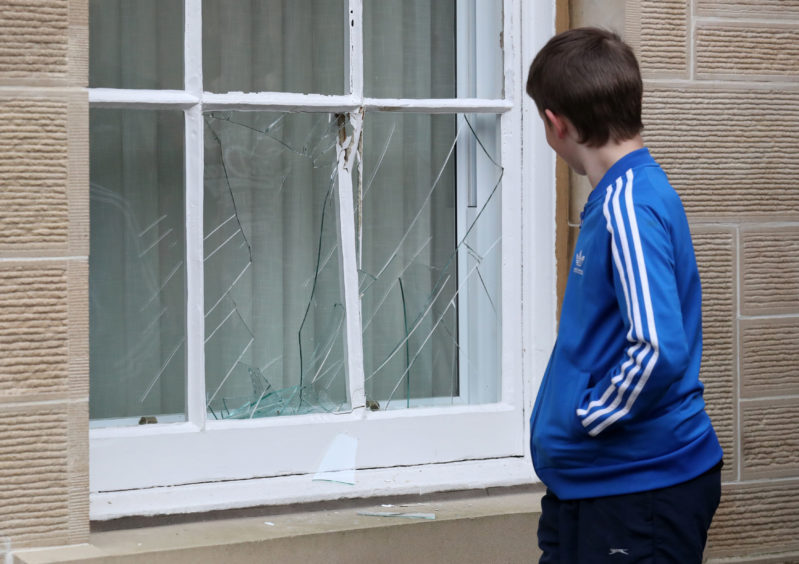 Damage to the Sheriff Court House window is viewed during the annual 'FasternÕs E'en Hand Ba' event on Jedburgh's High Street in the Scottish Borders.