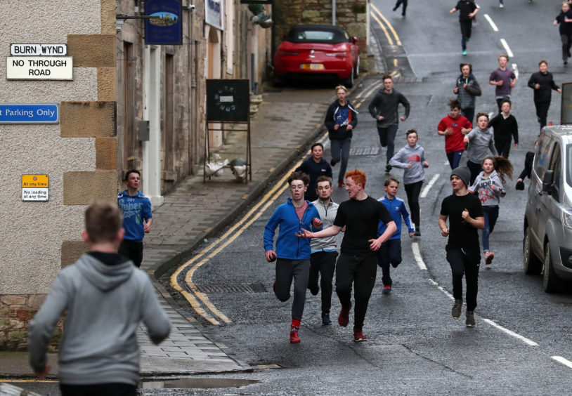 Boys run with the leather ball down a side street during the annual 'FasternÕs E'en Hand Ba' event on Jedburgh's High Street in the Scottish Borders.