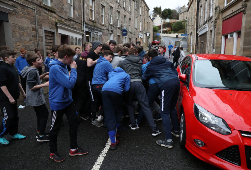 Boys tussle for the leather ball next to a car during the annual 'FasternÕs E'en Hand Ba' event on Jedburgh's High Street in the Scottish Borders.