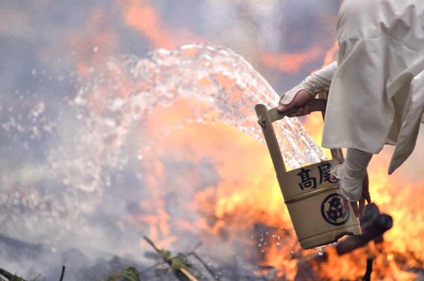 A Yamabushi Ascetic Monk throws water over the flames preparing the ground for the Hiwatari fire walking festival in a fire ritual called Saito Goma-ku at Yakuo-in temple in Takaosanguchi in Tokyo, Japan .