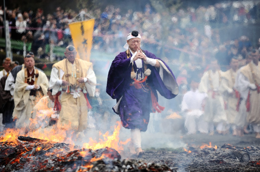 Yamabushi Ascetic Monks walking barefoot over the hot coals, and through flames which purify by burning all defilements away, pray for protection against sickness and calamity and for safety within the family during the Hiwatari fire walking festival in a fire ritual called Saito Goma-ku at Yakuo-in temple in Takaosanguchi in Tokyo, Japan.
