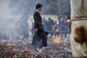 A salaryman walking barefoot over the hot coals, and through flames which purify by burning all defilements away, prays for protection against sickness and calamity and for safety within the family during the Hiwatari fire walking festival in a fire ritual called Saito Goma-ku at Yakuo-in temple in Takaosanguchi in Tokyo, Japan.