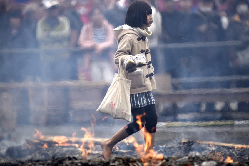 A young girl walking barefoot over the hot coals, and through flames which purify by burning all defilements away, pray for protection against sickness and calamity and for safety within the family during the Hiwatari fire walking festival in a fire ritual called Saito Goma-ku at Yakuo-in temple in Takaosanguchi in Tokyo, Japan .