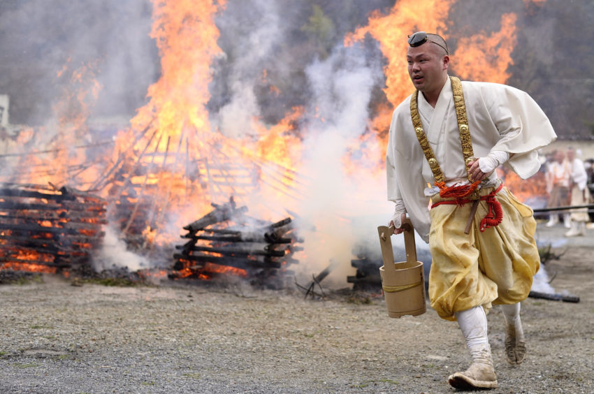 A Yamabushi Ascetic Monk prepares the ground for the Hiwatari fire walking festival in a fire ritual called Saito Goma-ku at Yakuo-in temple in Takaosanguchi in Tokyo, Japan.