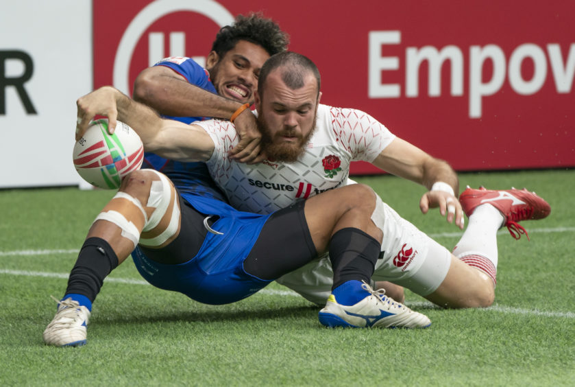 Tom Bowen of England reaches for the try line while being tackled by Elisapeta Alofipo of Samoa during rugby sevens action on Day 2 of the HSBC Canada Sevens at BC Place on March 10, 2019 in Vancouver, Canada.