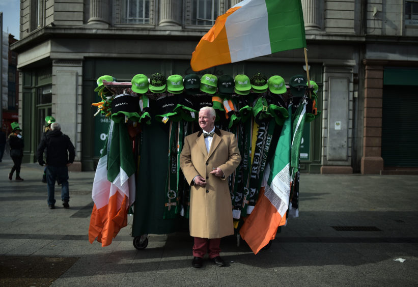 Street seller Michael Halliday stands beside his stall before the annual Saint Patrick's Day parade on March 17, 2019 in Dublin, Ireland. Saint Patrick, the patron saint of Ireland is celebrated around the world on St. Patrick's Day. According to legend Saint Patrick used the three-leaved shamrock to explain the Holy Trinity to Irish pagans in the 5th-century after becoming a Christian missionary.
