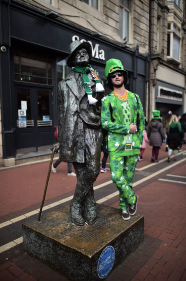 A reveller stands beside the James Joyce statue on O'Connell Street as he attends the Saint Patrick's Day parade on March 17, 2019 in Dublin, Ireland.