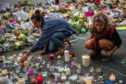 Women light candles next to flowers and tributes near Al Noor mosque on March 19, 2019 in Christchurch, New Zealand.