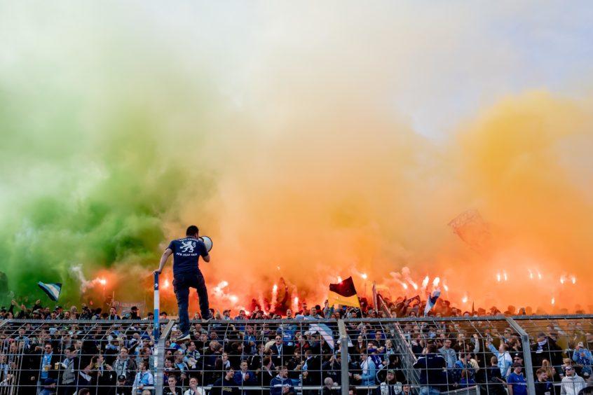 Fans of 1860 Muenchen start pyrotechnics during the 3. Liga match between TSV 1860 Muenchen and F.C. Hansa Rostock at Stadion an der Gruenwalder Straße in Munich, Germany.