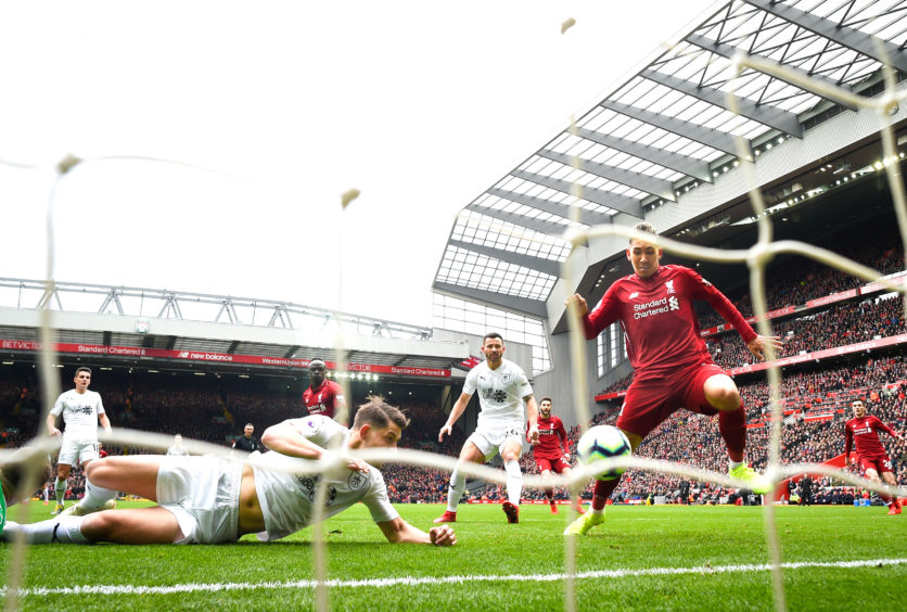 Roberto Firmino of Liverpool scores to make it 1-1 during the Premier League match between Liverpool FC and Burnley FC at Anfield .
