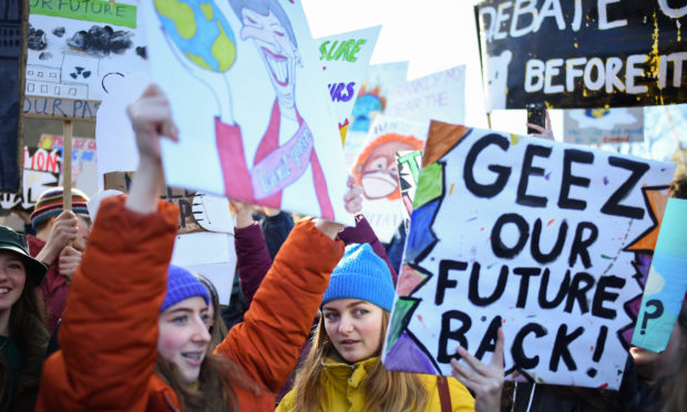 School children hold placards and shout slogans as they participate in a protest outside the Scottish Parliament.