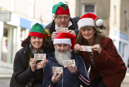 Forfar Action Network chairman Stuart Pirie (centre front) with FAN members, (clockwise) Jacqui Garvie, Tom O'Brien and Fiona Mulligan with five £10 notes for the 'Forfar Fifty'.