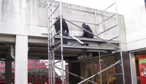 Workmen removing the old signs ahead of the 'Kirkcaldy Centre' revamp.