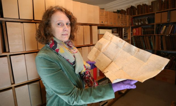 Curator Ingrid Thomson looks at a charter by Mary Queen of Scots in favour of John ,Lord of Glamis, of various lands in the shires of Forfar & Perth.