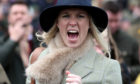 A racegoer reacts as she watches the action in the stands. Andrew Matthews/PA