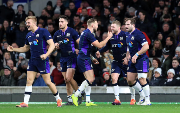 Finn Russell celebrates his try with team-mates at Twickenham.
