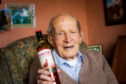 Alf Smith holding a bottle of whisky that bears his name.