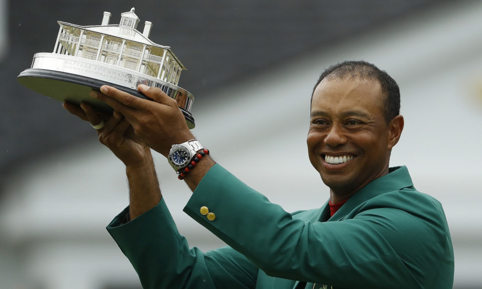 Tiger Woods wears his green jacket holding the winning trophy after the final round for the Masters golf tournament.