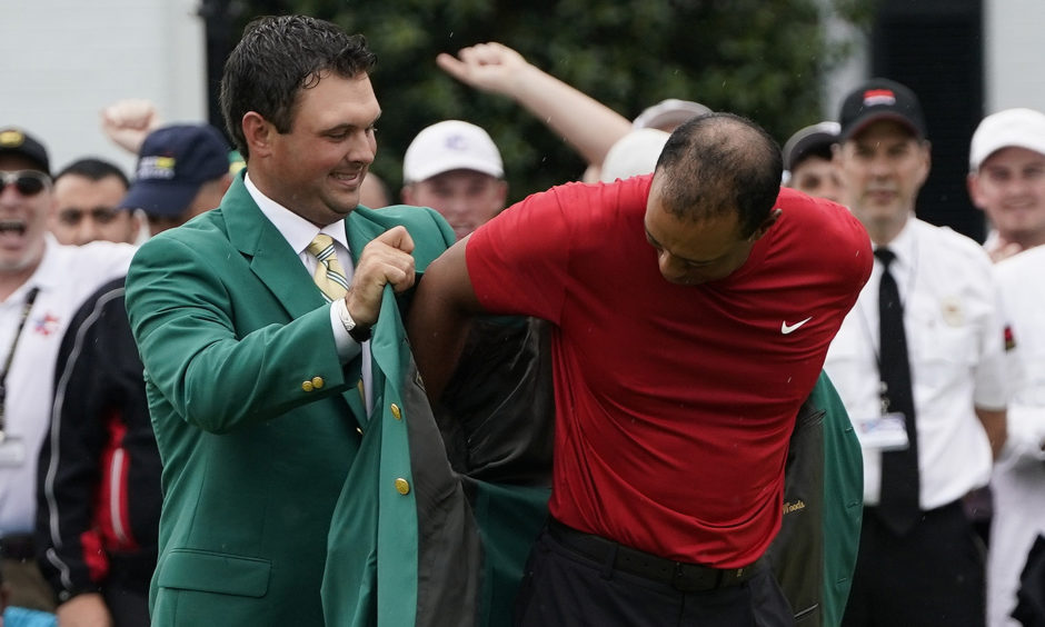 Patrick Reed helps Tiger Woods with his green jacket after Woods won the Masters golf tournament