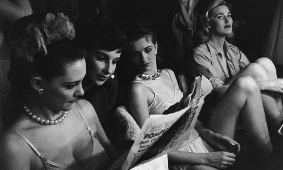 Bluebell Girls from London read the paper during an interval at the Lido club in the Champs-Elysees, Paris, November 1951. They are en route to Italy. Original Publication: Picture Post