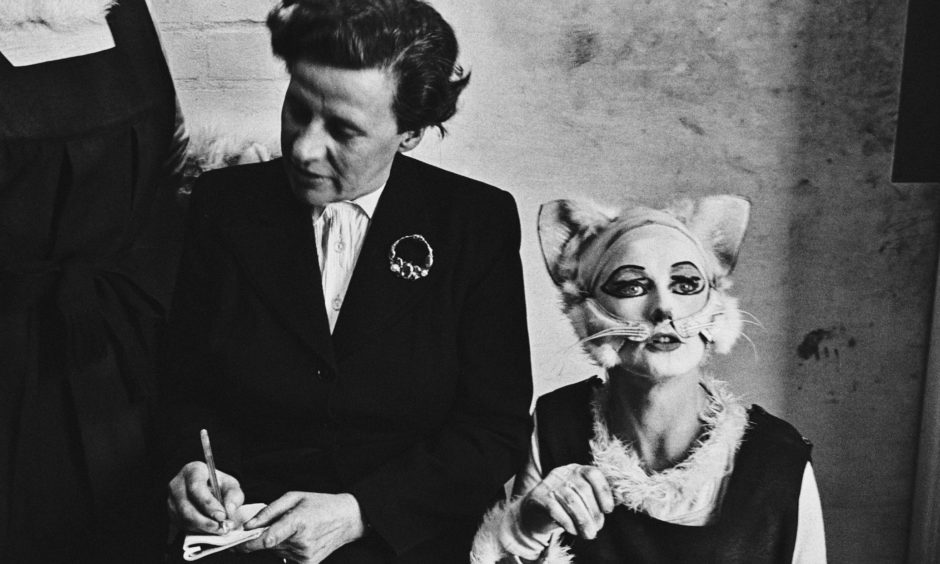 A female reporter interviewing characters dressed as cats in the backstage of a theater, UK, March 1952. Original Publication: Picture Post