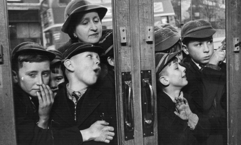 April 1953:  A group of children queuing outside a sweet shop.  Original Publication: Picture Post